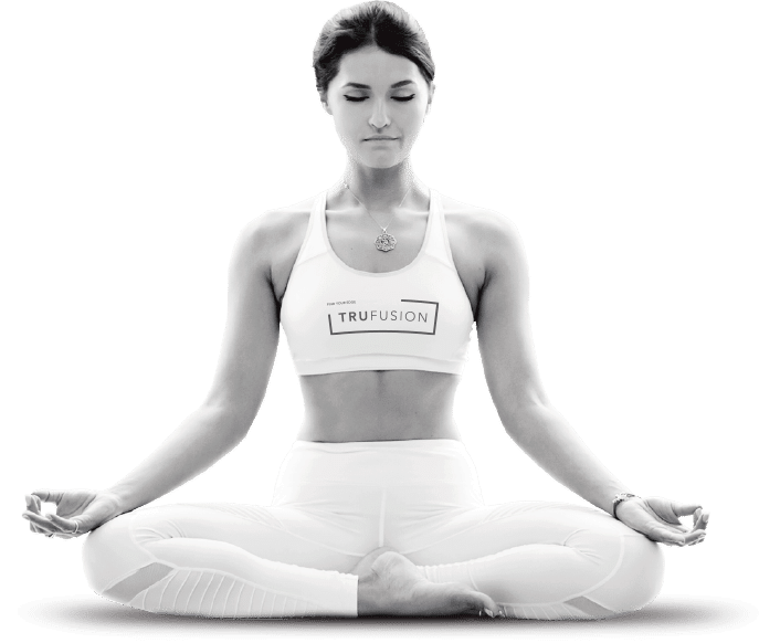 A woman wearing TruFusion branded workout clothing doing a yoga pose